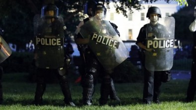 Police watch from Lafayette Park as protesters riot near the White House in Washington, DC.