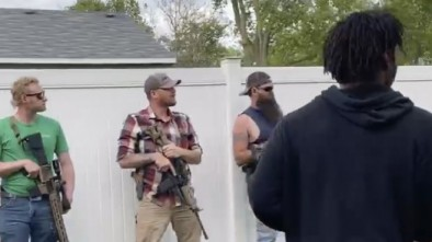 Protesters encounter a line of armed bystanders