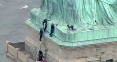 Woman Scales Statue of Liberty